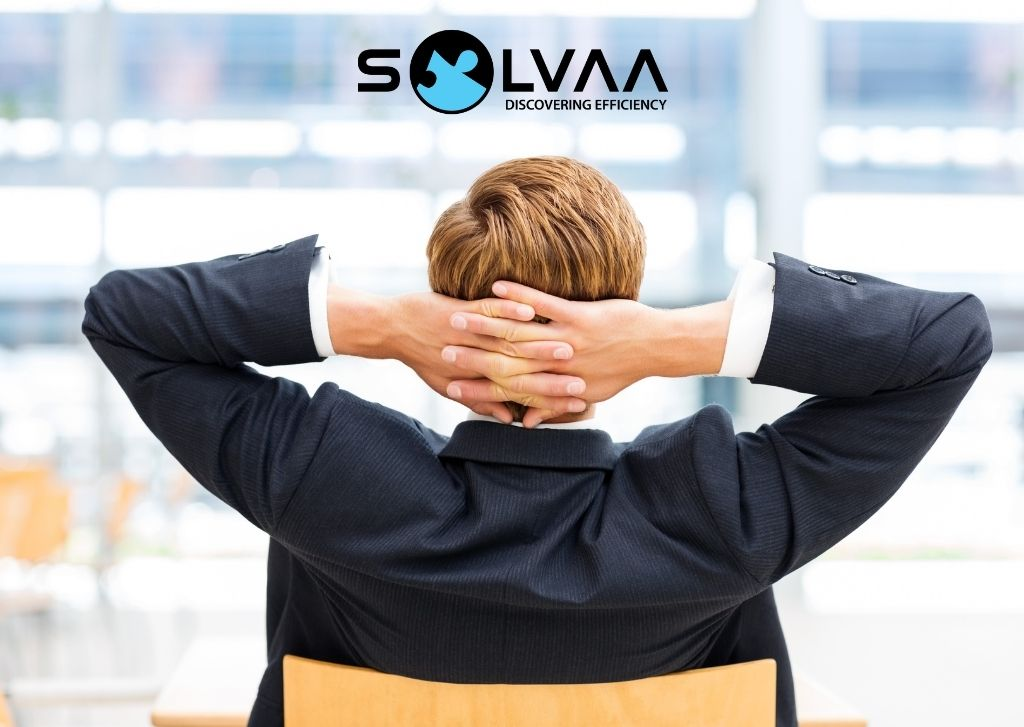Rear view of successful businessman relaxing in his office with his hands behind his head.